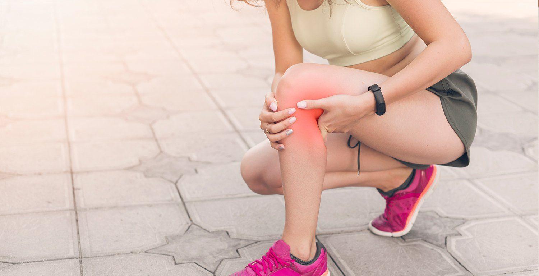 female athlete crouching in pain